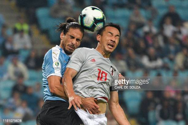 Uruguay's Martin Caceres and Japan's Shinji Okazaki go for a header during the Copa America football tournament Group C match between Uruguay and...