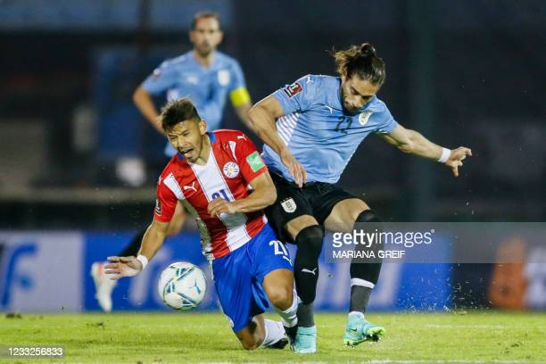 Uruguay's Martin Caceres and Paraguay's Oscar Romero vie for the ball during their South American qualification football match for the FIFA World Cup...