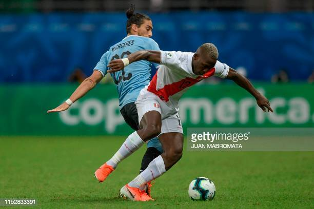 Uruguay's Martin Caceres and Peru's Luis Advincula vie for the ball during their Copa America football tournament quarterfinal match at the Fonte...