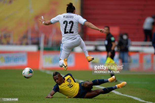 Uruguay's Martin Caceres jumps over Ecuador's Pervis Estupinan during their 2022 FIFA World Cup South American qualifier football match at the...