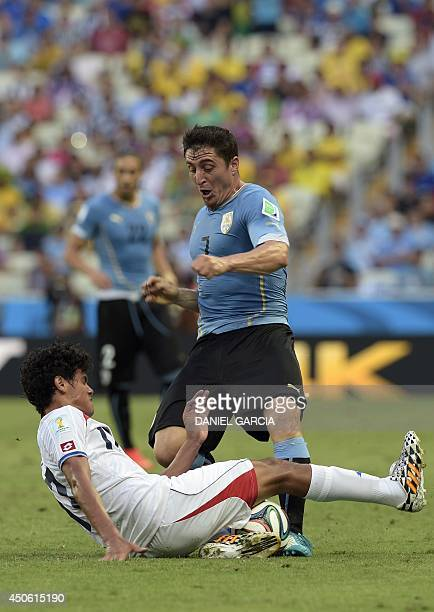 Uruguay's midfielder Cristian Rodriguez and Costa Rica's midfielder Michael Barrantes vie for the ball during a Group D football match between...