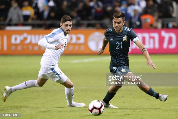 Uruguay's midfielder Federico Valverde fights for the ball with Argentina's forward Paulo Dybala during the friendly football match between Argentina...