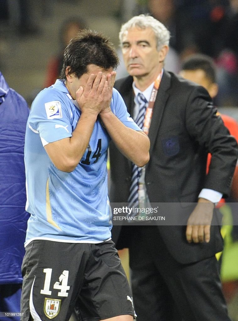 Uruguay's midfielder Nicolas Lodeiro (L) reacts after receiving a red card as France's coach Raymond Domenech looks at him during their Group A first round 2010 World Cup football match on June 11, 2010 at Green Point stadium in Cape Town. NO