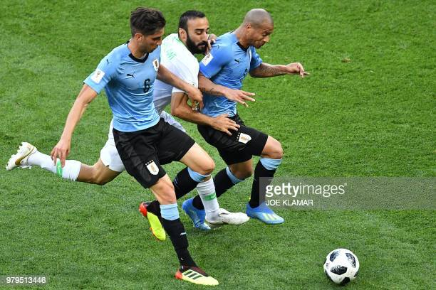 Uruguay's midfielder Rodrigo Bentancur and Uruguay's midfielder Carlos Sanchez fights for the ball with Saudi Arabia's forward Mohammed AlSahlawi...