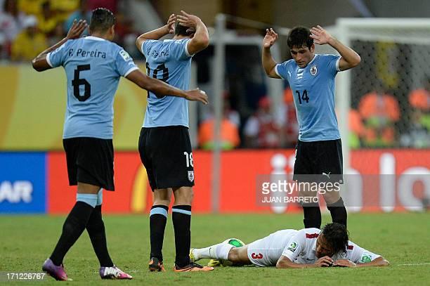 Uruguay's midfielders Alvaro Pereira Gaston Ramirez and Nicolas Lodeiro gesture after Tahiti's forward Marama Vahirua was fouled during their FIFA...