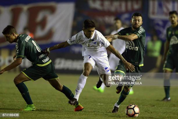 Uruguay's Nacional forward Kevin Ramirez vies for the ball with Brazil's Chapecoense midfielders Rossi and Andrei Girotto during their Libertadores...