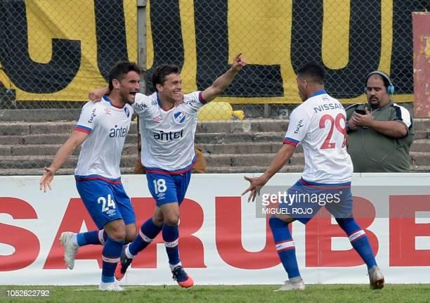 Uruguay's Nacional forward Sebastian Fernandez celebrates with teammates Argentine Gonzalo Ruben Bergessio and Brian Ocampo after scoring against...