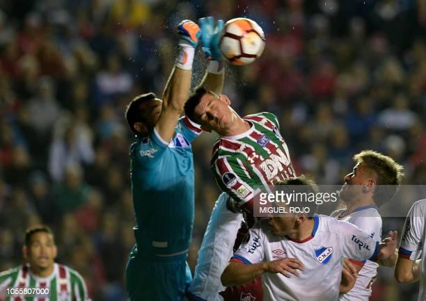 Uruguay's Nacional goalkeeper Esteban Nestor Conde jumps to grab the ball next to Brazil's Fluminense Roger Ibanez during their Copa Sudamericana...