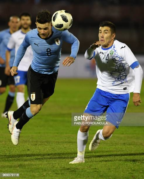 Uruguay's Nahitan Nandez vies for the ball with Uzbekistan's Akramjon Komilov during their international friendly football match between Uruguay and...