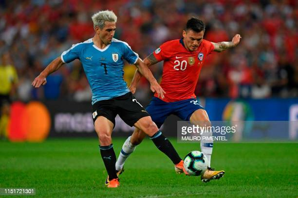 Uruguay's Nicolas Lodeiro and Chile's Charles Aranguiz vie for the ball during their Copa America football tournament group match at Maracana Stadium...