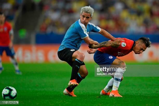 Uruguay's Nicolas Lodeiro and Chile's Eduardo Vargas vie for the ball during their Copa America football tournament group match at Maracana Stadium...