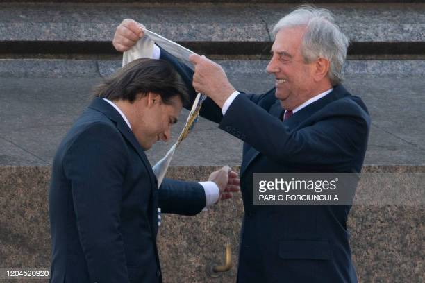 Uruguay's outgoing President Tabare Vazquez places the presidential sash on incoming President Luis Lacalle Pou during the inauguration ceremony at...