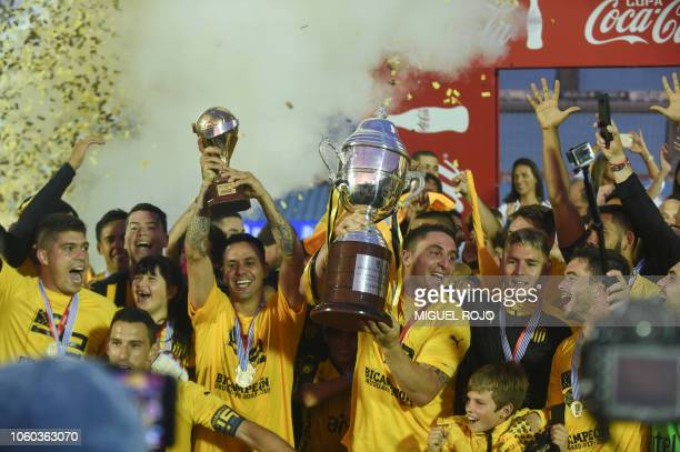 Uruguay's Penarol midfielder Cristian Rodriguez holds the cup during the celebration of the players after defeating Uruguay's Nacional during the...