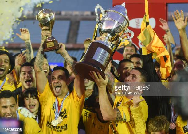 Uruguay's Penarol midfielder Cristian Rodriguez holds the Uruguayan Championship Cup next to Uruguay's Penarol forward Fabian Estoyanoff during the...