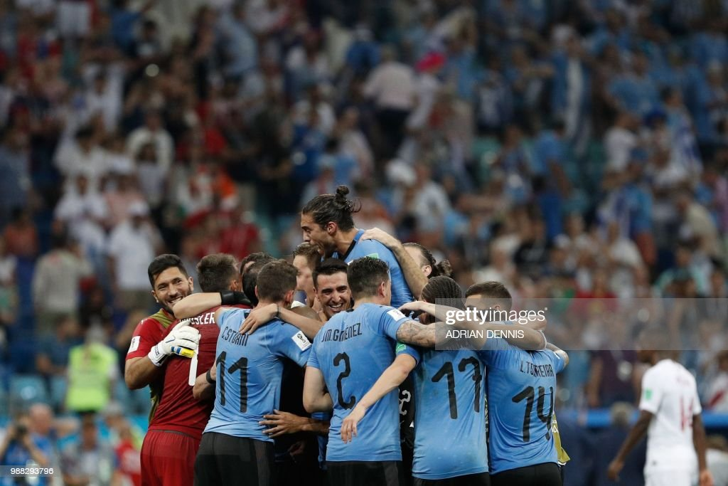 TOPSHOT - Uruguay's players celebrate their win during the Russia 2018 World Cup round of 16 football match between Uruguay and Portugal at the Fisht Stadium in Sochi on June 30, 2018. - Uruguay sent Cristiano Ronaldo and Portugal crashing out of the World Cup on Saturday as a pair of stunning goals from Edinson Cavani gave the South Americans a 2-1 victory. (Photo by Adrian DENNIS / AFP) / RESTRICTED