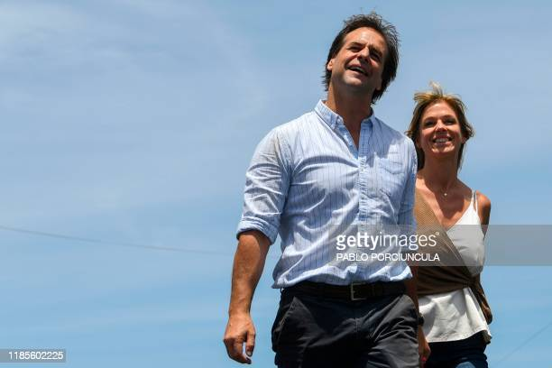 Uruguay's presidentelect Luis Lacalle Pou gestures next to his wife Lorena Ponce de Leon during a rally to celebrate his victory in Montevideo on...