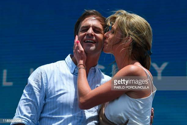 Uruguay's presidentelect Luis Lacalle Pou is kissed by his wife Lorena Ponce de Leon during a rally to celebrate his victory in Montevideo on...