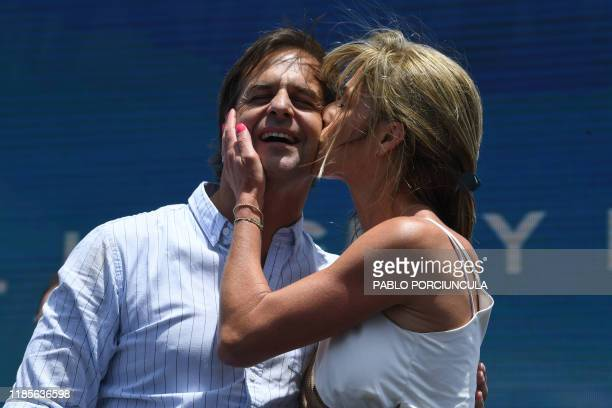 TOPSHOT Uruguay's presidentelect Luis Lacalle Pou is kissed by his wife Lorena Ponce de Leon during a rally to celebrate his victory in Montevideo on...