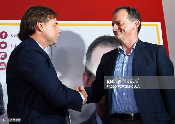Uruguays presidential candidate for the Nacional party Luis Lacalle Pou shakes hands with former presidential candidate Guido Manini Rios of the...