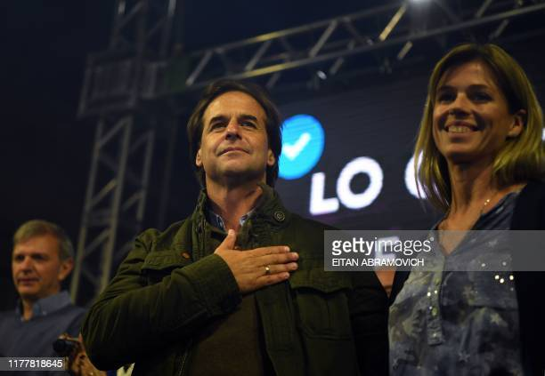 Uruguay's presidential candidate Luis Lacalle Pou of the opposition Partido Nacional party gestures next to his wife Lorena Ponce de Leon during a...