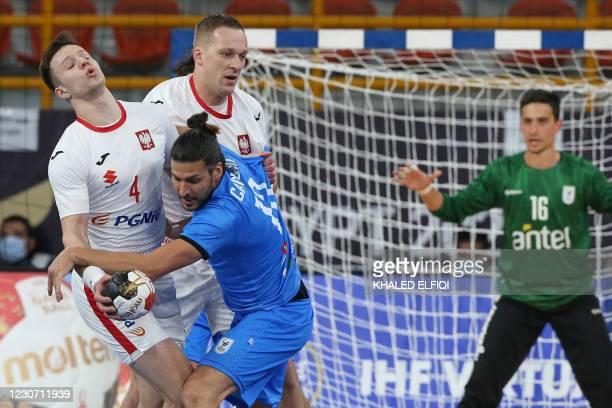 Uruguay's right back Maximo Cancio vies for the ball with Poland's centre back Michal Olejniczak during the 2021 World Men's Handball Championship...