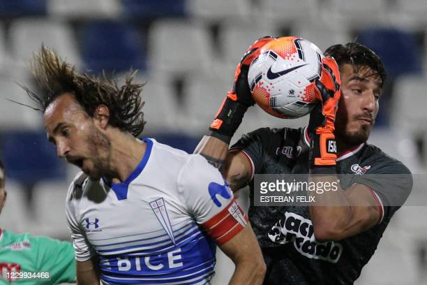 Uruguay's River Plate goalkeeper Gaston Olveira cathes the ball next to Chile's Universidad Catolica Jose Pedro Fuenzalida during their closed-door...