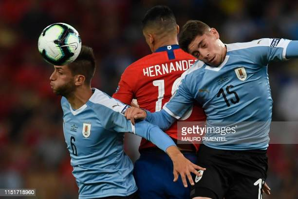Uruguay's Rodrigo Bentancur and Federico Valverde vie for the ball with Chile's Pedro Pablo Hernandez during their Copa America football tournament...