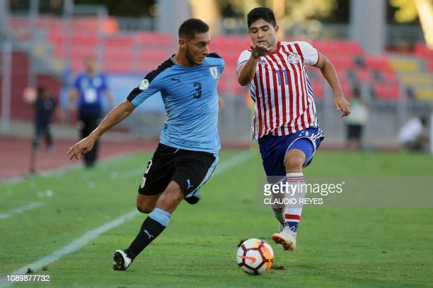 Uruguay's Sebastian Caceres vies for the ball with Paraguay's Antonio Marin during their South American U20 football match at Fiscal stadium in Talca...