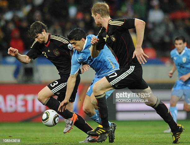 Uruguay's striker Luis Suarez fights for the ball with Germany's defender Arne Friedrich and Germany's defender Per Mertesacker during the 2010 World...