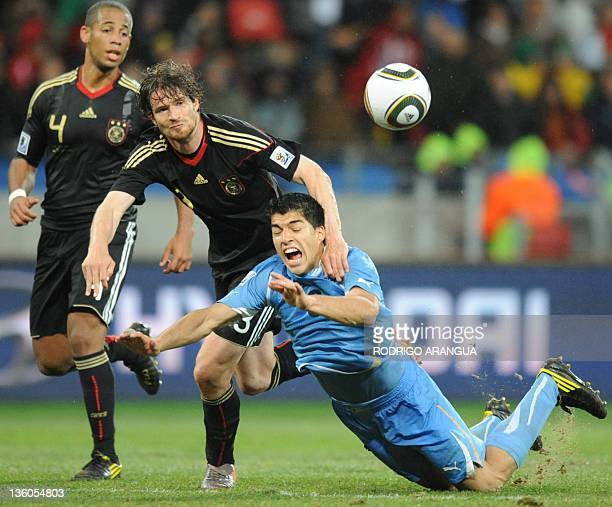 Uruguay's striker Luis Suarez is grabbed by Germany's defender Arne Friedrich as they fight for the ball during the 2010 World Cup third place...