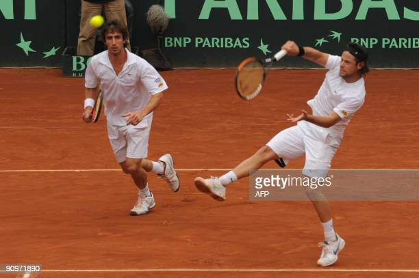 Uruguay's tennis player Marcel Felder hits the ball while his partner Pablo Cuevas watches during their Davis Cup's Americas Zone Group 1 Doubles...