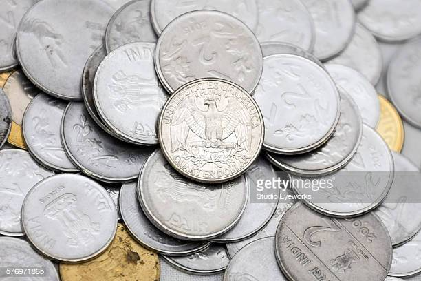 Us quarter over a heap of indian currency coins