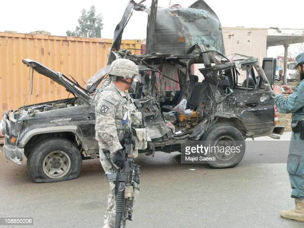 Us troops and Afghan Policemen inspect the wreckage of the Deputy Governor's car after an attack by a suicide bomber on January 29, 2010 in Kandahar,...