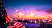 Usa Celebration With Hands Holding Sparklers And American Flag At Sunset With Fireworks