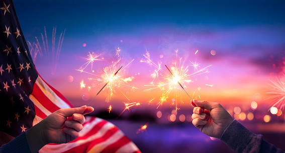 Usa Celebration With Hands Holding Sparklers And American Flag At Sunset With Fireworks 1219800862