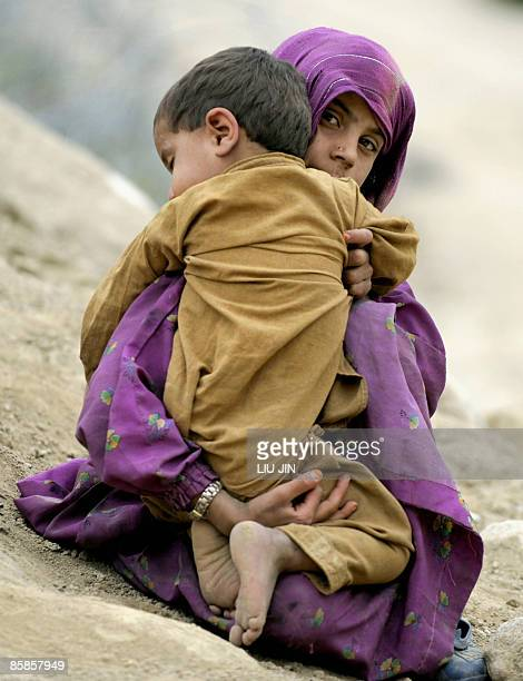 Afghanistan-unrest-military-aid-development,FOCUS by Charlotte McDonald-Gibson An Afghan girl holds her little brother sleeping on shoulders in...