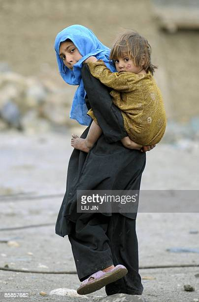 Afghanistan-unrest-military-aid-development,FOCUS by Charlotte McDonald-Gibson An Afghan young woman carries her little sister in Naray, in...