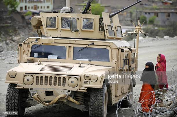 Afghanistan-unrest-military-security, FOCUS by Charlotte McDonald-Gibson Two Afghan girls look at a US Army Humvee from 1st Infantry Division on a...