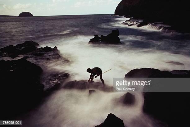 USA,Hawaii,Molakai,fisherman spearing fish along rugged coast
