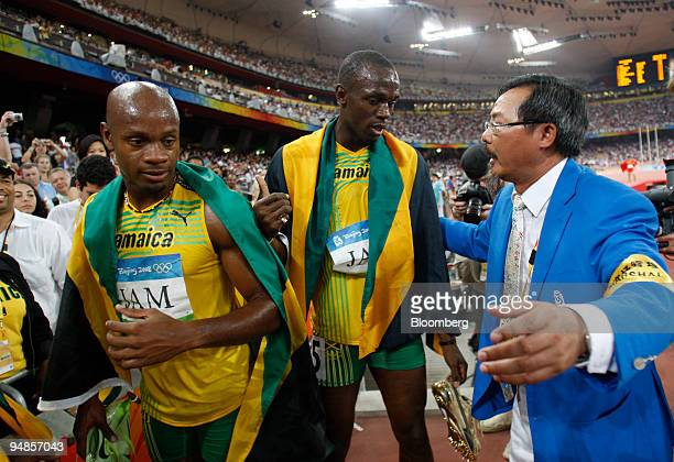Usain Bolt and Asafa Powell left both of Jamaica are urged by an Olympic official to leave the track area after a lengthy victory lap following their...