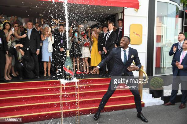 Usain Bolt demonstrates a sabrage at the Mumm marquee on Melbourne Cup Day at Flemington Racecourse on November 05, 2019 in Melbourne, Australia.