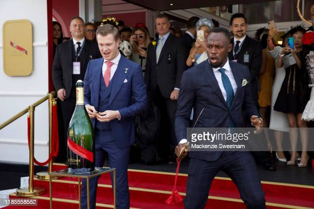 Usain Bolt demonstrates a sabrage at the Mumm marquee on Melbourne Cup Day at Flemington Racecourse on November 05 2019 in Melbourne Australia
