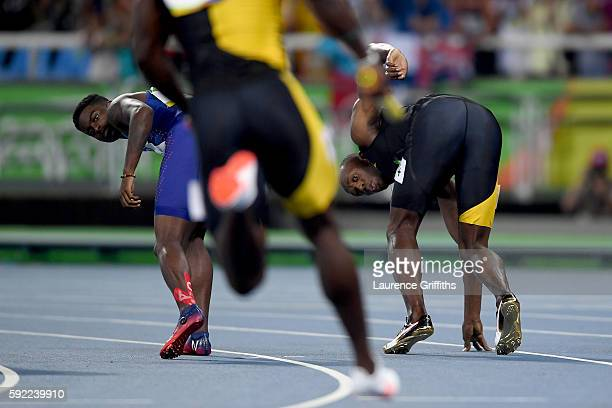 Usain Bolt of Jamaica and Trayvon Bromell of the United States wait for batons to be passed in the Men's 4 x 100m Relay Final on Day 14 of the Rio...