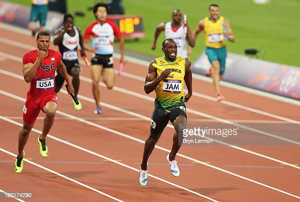 Usain Bolt of Jamaica approaches the finish line ahead of Ryan Bailey of the United States to win gold and set a new world record of 36.84 during the...