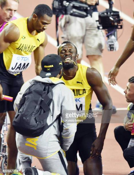 Usain Bolt of Jamaica bites his necklace after failing to finish with a hamstring injury on the anchor leg of the men's 4x100meter relay final at the...