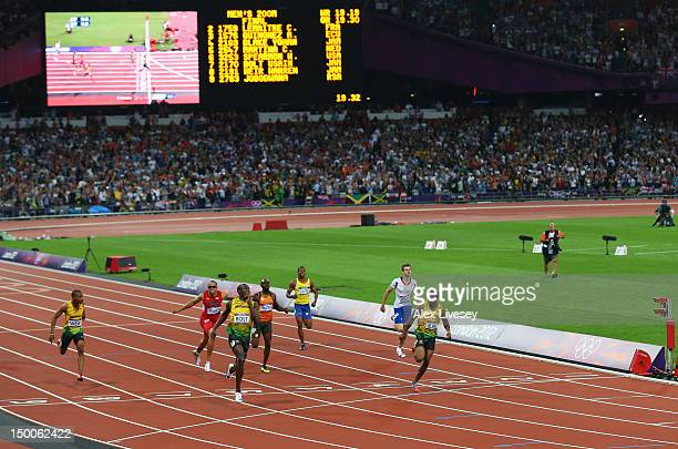 Usain Bolt of Jamaica celebrates as he crosses the finish line ahead of Warren Weir of Jamaica Wallace Spearmon of the United States Churandy Martina...