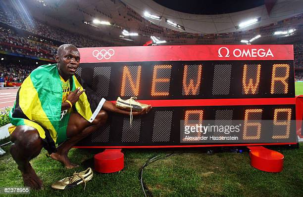 Usain Bolt of Jamaica celebrates next to the scoreboard winning the Men's 100m Final and the gold medal at the National Stadium on Day 8 of the...