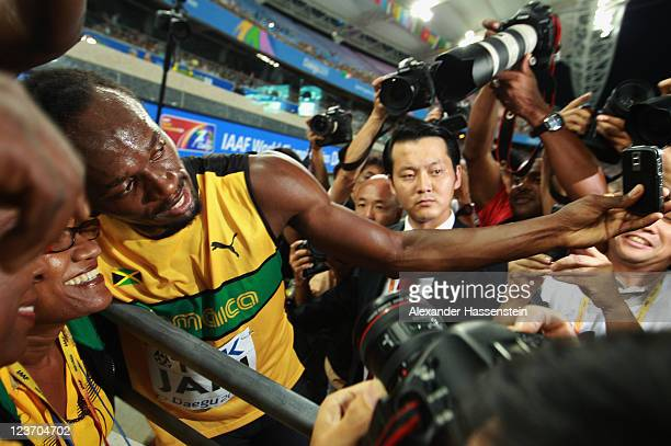 Usain Bolt of Jamaica celebrates victory and a new world record with his mother Jennifer Bolt following the men's 4x100 metres relay final during day...