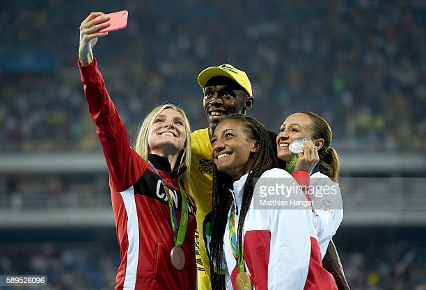 Usain Bolt of Jamaica celebrates winning the Men's 100 meter final with Women's Heptathlon gold medalist Nafissatou Thiam of Belgium silver medalist...