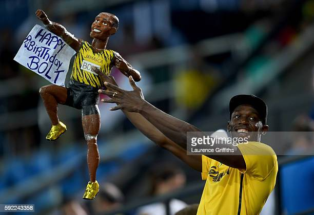 Usain Bolt of Jamaica celebrates with a fan's likeness of him after winning the Men's 4 x 100m Relay Final on Day 14 of the Rio 2016 Olympic Games at...